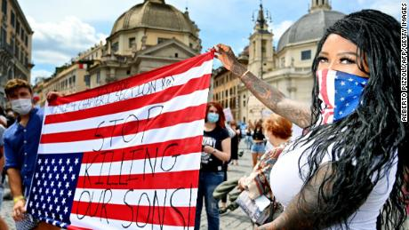 Protesters in Rome are holding the American flag upside down.