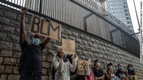 A small crowd gathers in front of the American embassy in Hong Kong.