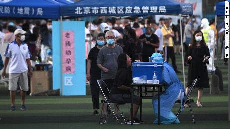 A health worker in a protective suit takes a swab test from a woman at a test center set up for people who have visited or live near Xinfadi Market in Beijing.