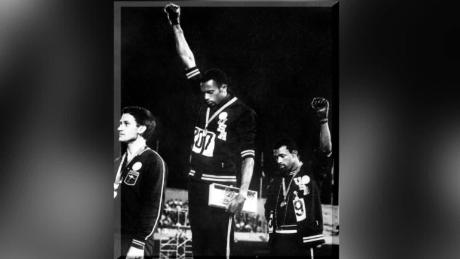 Tommie Smith (center) and John Carlos (right) on the podium at the 1968 Mexico Olympics.