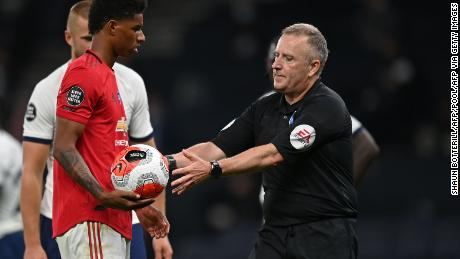 Referee Jonathan Moss takes the ball to Marcus Rashford after he wrongly awarded a penalty.