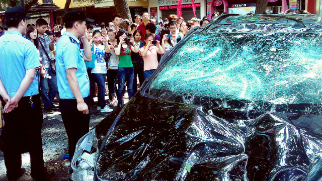 People photograph a Japanese car damaged during a protest against the nationalization of Japan. disputed islands of Diaoyu, also known in Japan as the Senkaku Islands, in the Chinese city of Xi & # 39; September 15, 2012