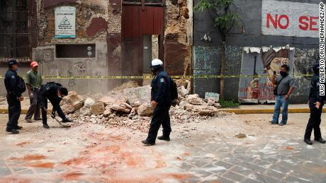 A police officer is removing trash from a building damaged in the earthquake in Oaxaca, Mexico.