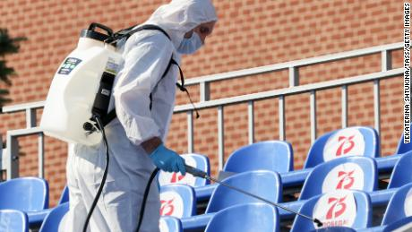 A sanitary worker in protective gear sprays disinfectant on the seats in Red Square before the procession.