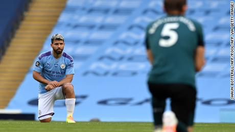 Manchester City striker Sergio Aguero (L) and Burnley defender James Tarkowski kneel in support of the Black Lives Matter movement.