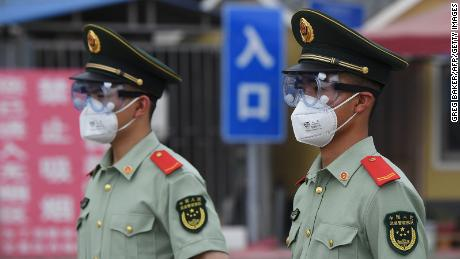 Paramilitary officers wear masks and goggles as they stand guard at the entrance to Xinfadi Indoor Market in Beijing on June 13th.