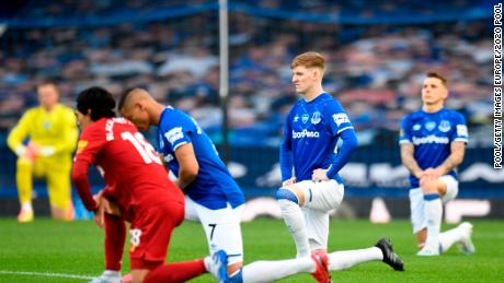 Players and officials kneel in a sign of the Black Lives Matter movement ahead of the Merseyside derby between Everton and Liverpool at Goodison Park.