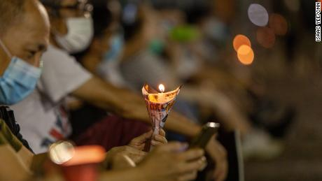 A man holds a candle on Thursday at the vigil.