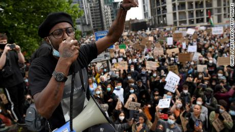 The activist addresses those gathered near the American embassy in London.