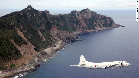 A Japanese military plane flies over Senakuku / Diaoyu Island in this file.
