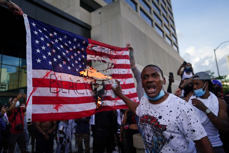 Protesters burn a flag in front of the CNN Center on May 29 in Atlanta, Georgia.