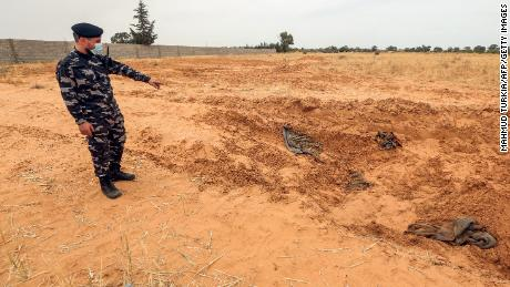 A member of the security forces linked to the Libyan government of the National Agreement (GNA), the Interior Ministry, points to the reported location of a mass grave in the city of Tarhuni, about 65 kilometers southeast of the capital Tripoli on June 11, 2020.
