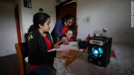 The family listens for an hour to radio lectures from their home in Funza, Colombia, where they have no internet connection.