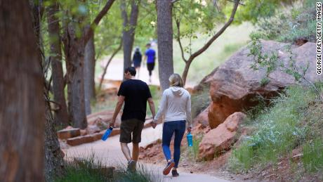 Hikers walking on a paved trail in Zion National Park in Utah, Utah, which was closed due to a pandemic.
