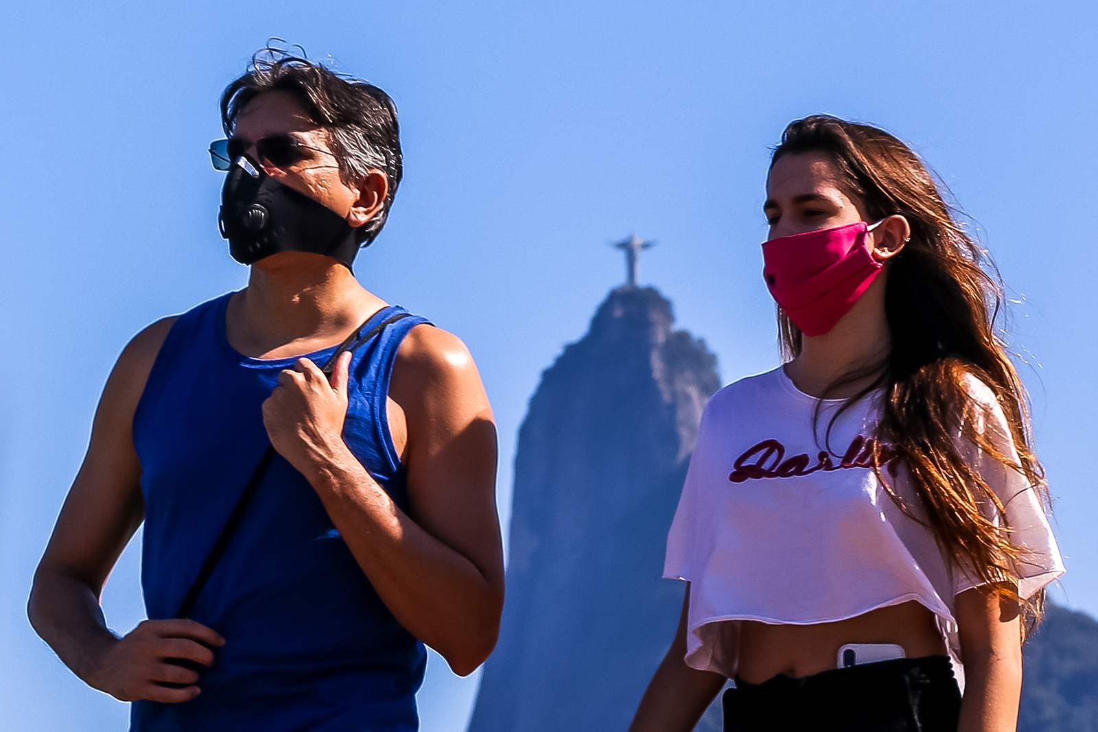 People wearing face masks enjoy the weather at Botafogo Cove, as the Christ the Redeemer statue is seen in the distance, on July 5, in Rio de Janeiro, Brazil.