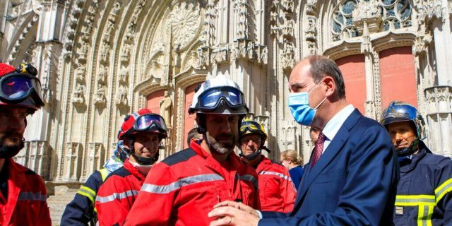 French Prime minister Jean Castex, right, wearing a face mask meets firefighters after the blaze at the Gothic St. Peter and St. Paul Cathedral, in Nantes, western France, Saturday, July 18, 2020.