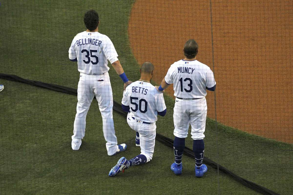 Los Angeles Dodgers' Cody Bellinger, left, and Max Muncy, right, put their hands on Mookie Betts during the national anthem prior to an opening day baseball game Thursday, July 23, 2020, in Los Angeles.