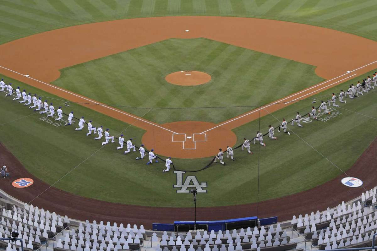 Members of the Los Angeles Dodgers and the San Francisco Giants kneel during a moment of silence prior to an opening day baseball game Thursday, July 23, 2020, in Los Angeles.