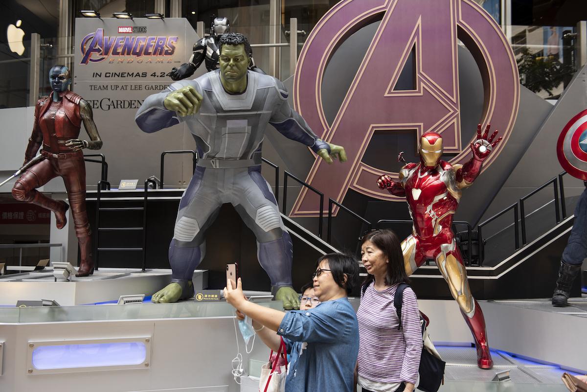 Pedestrians taking a selfie with Marvel figures