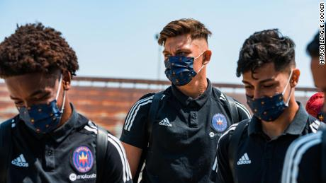 Members of the Chicago Fire FC don masks on their way to training.