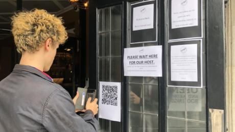 Plastic screens, search applications and service tables. English pubs reopen on a bitter day