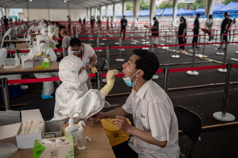 A health worker wearing a protective suit, face mask and face shield takes a swab test on a man