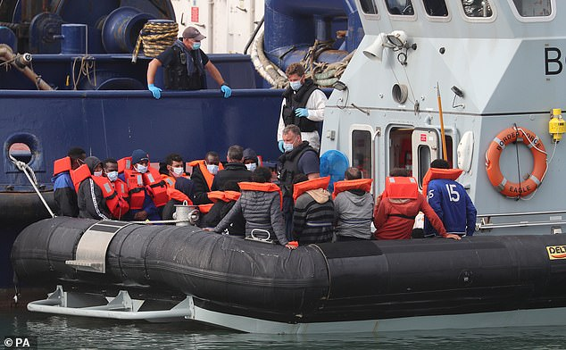 Pictured:A group of people thought to be migrants are brought into Dover, Kent, by Border Force officers following a number of small boat incidents in the Channel, August 15, 2020.New figures show that more than 1,000 migrants crossed to the UK in just ten days this month