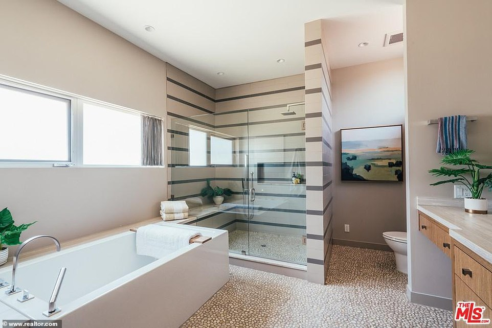 Great for a long and relaxing spa day: A bathroom is attached and offers a rectangular bathtub with a steam shower