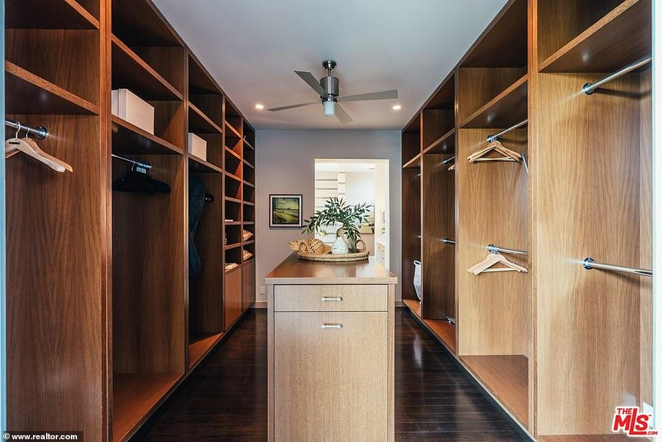 Clothes minded: A dark wood walk-in closet is every girl's dream with dark floors and an island perfect for storing costume jewelry and fancy purses