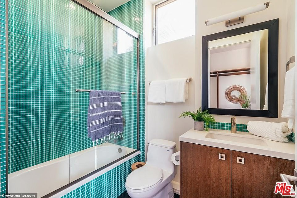 Small but sensible: And the second bathroom includes a green tiled shower next to a single sink vanity