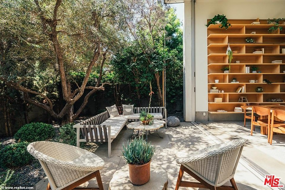 An indoor/outdoor California style: The living room opens up to a small but stylish outdoor area with mature trees