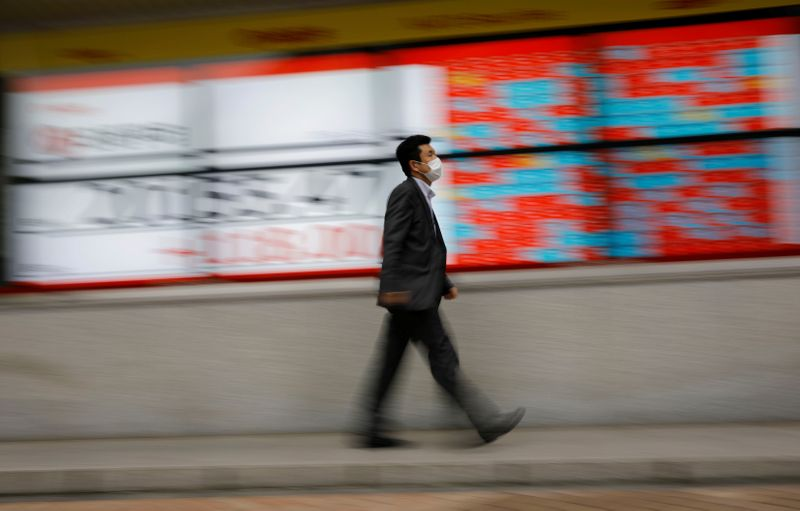 © Reuters. FILE PHOTO: A man wearing a protective face mask, following the coronavirus disease (COVID-19) outbreak, walks in front of a stock quotation board outside a brokerage in Tokyo