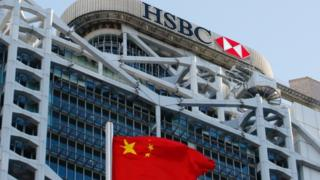 A Chinese national flag flies in front of HSBC headquarters in Hong Kong.