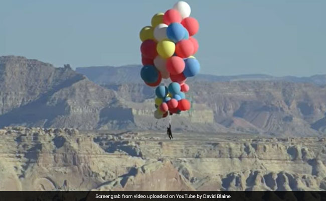 Dardeville flies through the sky with 52 helium balloons. Watch