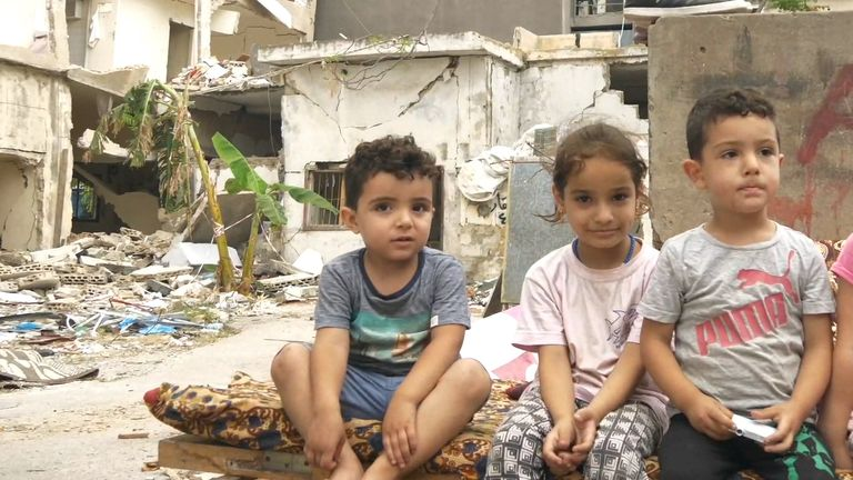 A Syrian refugee family sits on the rubble of their destroyed building in Beirut