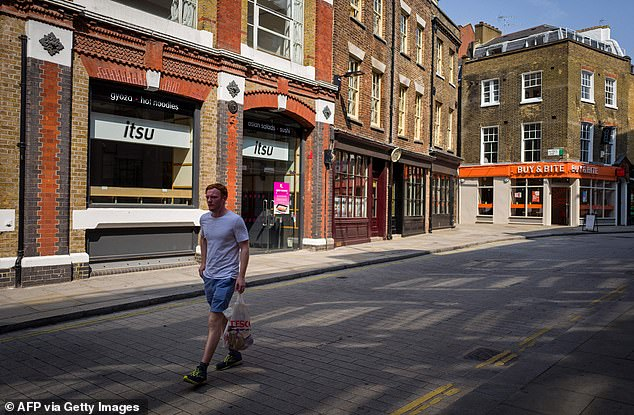 A pedestrian passes through shops and food outlets on an empty shopping street in London on August 12th