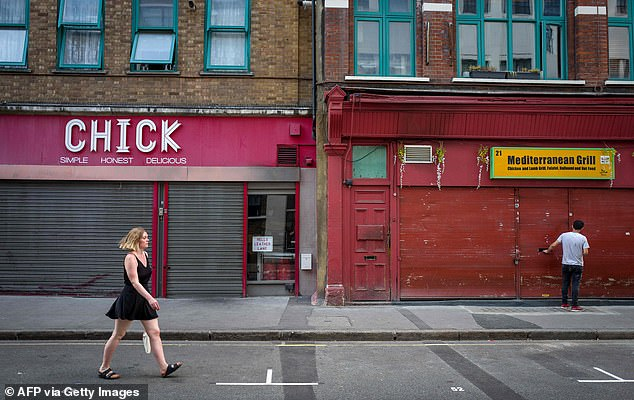 A pedestrian passes by closed storefronts on an empty London shopping street last month