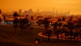 Downtown San Francisco can be seen from Dolores Park under an orange sky
