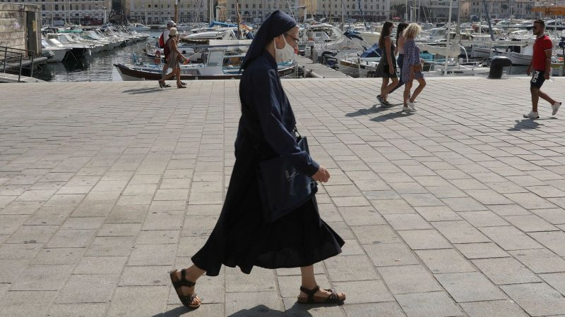 A nun wearing a protective face mask walks at the Old Port in Marseille
