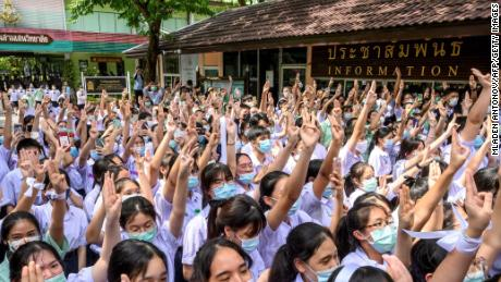 Students perform a three-toed salute at Samsen School to demand less strict school rules and more tolerance and respect during a protest in Bangkok on October 2, 2020.