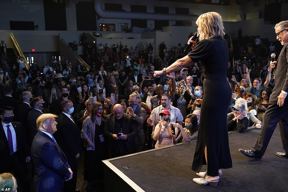Denise Gault leads the church in prayer to President Donald Trump, who has taken a seat near the front of the International Church in Las Vegas