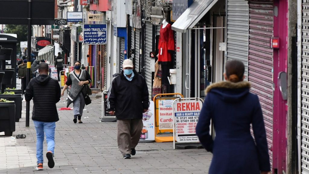 """Pedestrians wearing protective face masks walk past shops in the Handsworth area of Birmingham, central England on August 22, 2020, as Britain's second-city, home to more than one million people, was made an """"area of enhanced support"""", because of concern about a spike in cases of the novel coronavirus. (Photo by JUSTIN TALLIS / AFP) (Photo by JUSTIN TALLIS/AFP via Getty Images)"""