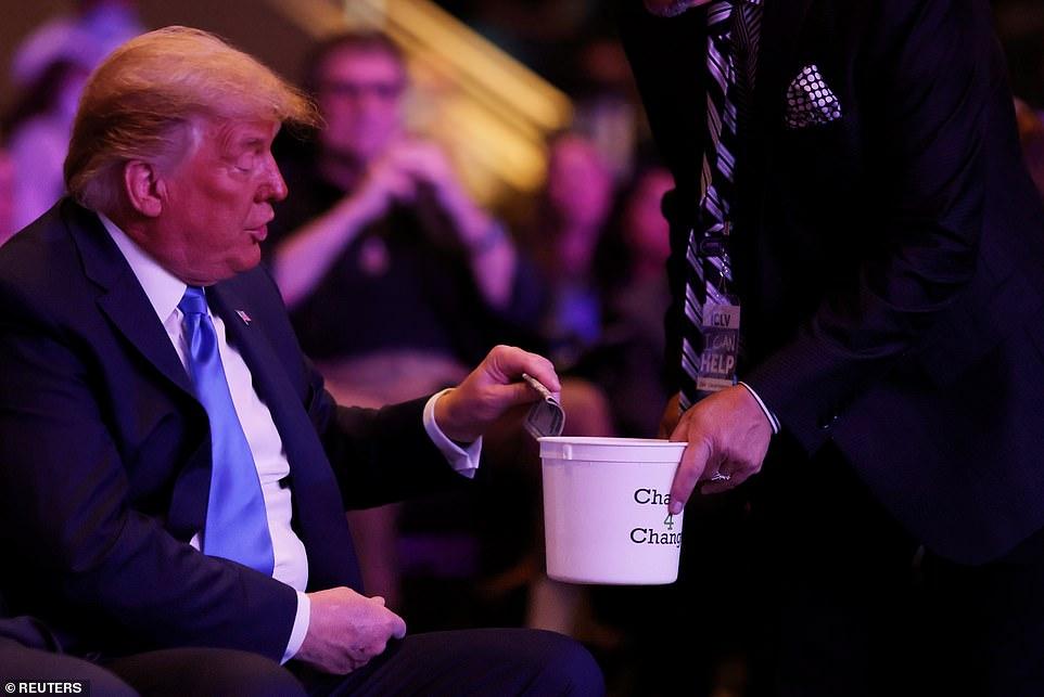 President Donald Trump is seen putting a $ 20 bunch into a token jar during Sunday Mass at Las Vegas International Church.