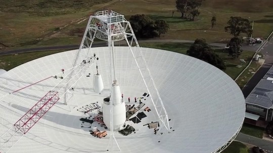 Work crews carry out important upgrades and repairs to the 70 meter (230 ft) radio antenna in Deep Space Station 43 in Canberra, Australia. In this segment, one of the antenna's white feed cones (which houses parts of the antenna receivers) is driven by a jack. (Credits: CSIRO)