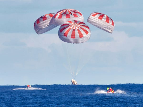 SpaceX's Crew Dragon guided by four parachutes takes off into the Atlantic Ocean off the coast of Florida