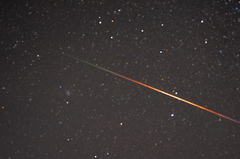 It sparkles with a bold red to orange streak across the starry sky.