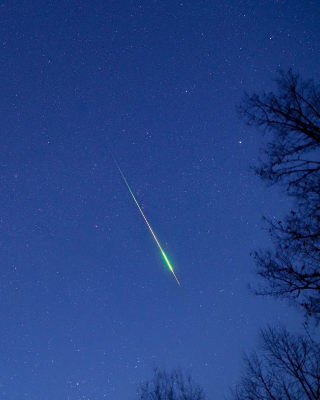 A long and bright colored meteor streak against a bluish sky.
