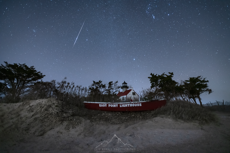A thin line in the sky over the sand dunes with a lighthouse sign.