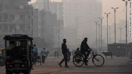 People make their way along the street amidst the conditions of smog in New Delhi on November 15, 2020.