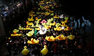 Protesters carry inflatable ducks on their way to the 11th Infantry Barracks.